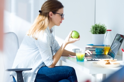 Pretty Young Woman Eating An Apple And Working At Home by nenetus